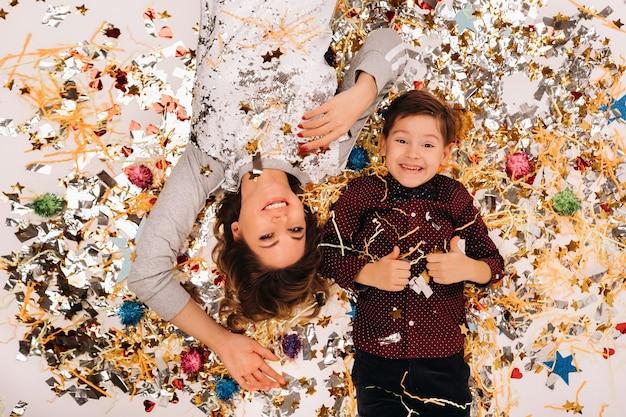 Moeder en zoon liggen in confetti op een witte achtergrond op de vloer. een vrouw en een jongen in confetti op een witte achtergrond.