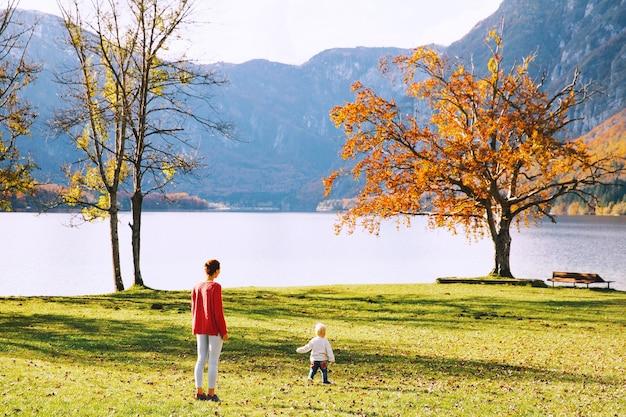 Moeder en zoon lopen buiten. herfst op het meer van bohinj, slovenië, europa. vrouw en haar kind blij met de natuur. familie brengt de herfstvakantie door in een prachtig bergmeer.