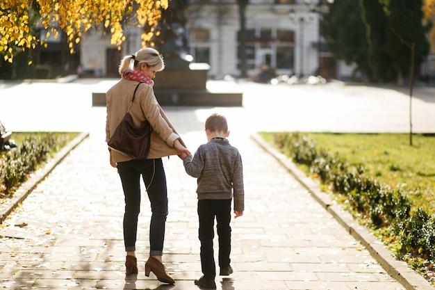 Moeder en zoon lopen buiten in de herfst