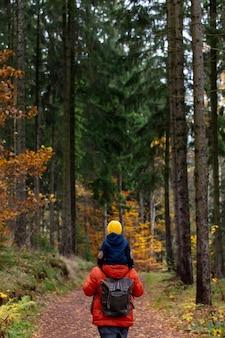 Moeder en zoon lopen in de herfst door het bos