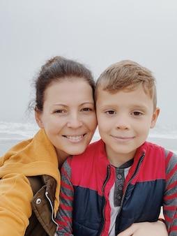Moeder en zoon lopen langs het mistige strand en maken een selfie aan de telefoon. portret van gelukkige moeder en kindjongen.