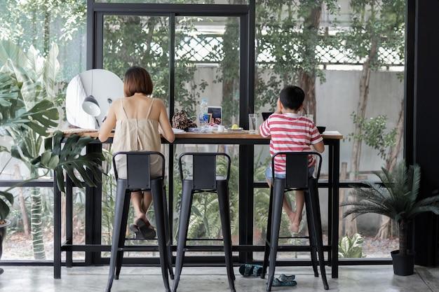 Moeder en zoon lunchen samen in café.