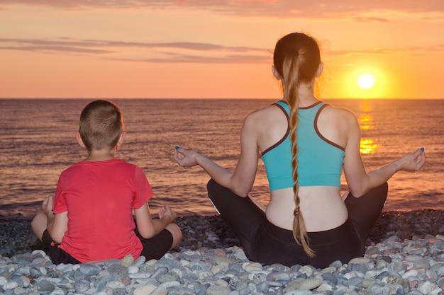Moeder en zoon mediteren op het strand in lotushouding. uitzicht vanaf de achterkant, zonsondergang