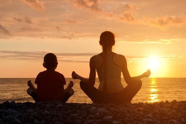 Moeder en zoon mediteren op het strand in lotushouding