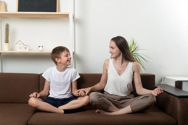 Moeder en zoon mediteren zittend op de bank