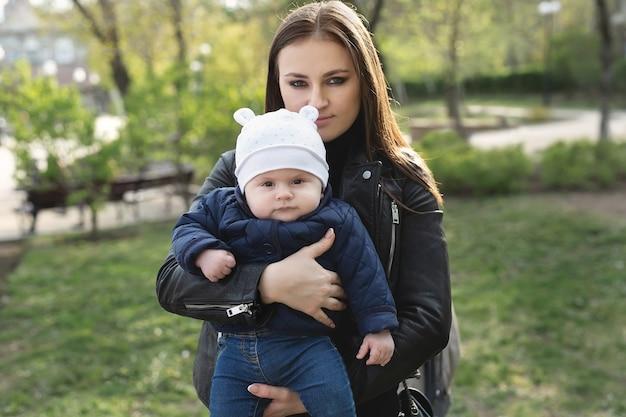 Moeder en zoon met een klein kind lopen in een bos of park van de lente