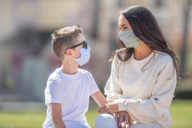 Moeder en zoon met gezichtsmaskers kijken elkaar aan terwijl ze buiten zitten.