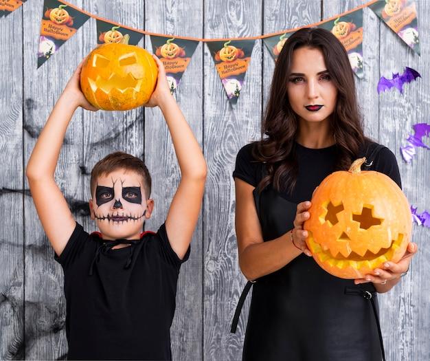 Moeder en zoon met halloween-pompoenen