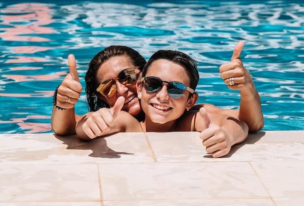Moeder en zoon met zonnebril leunen op een zonnige zomerdag op de rand van het zwembad