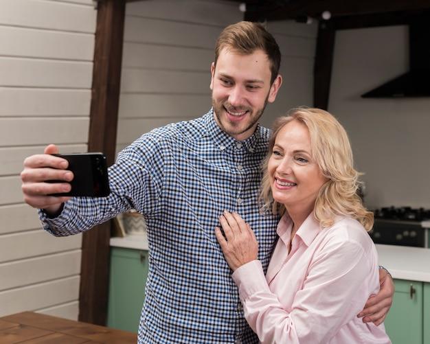 Moeder en zoon nemen een selfie in de keuken