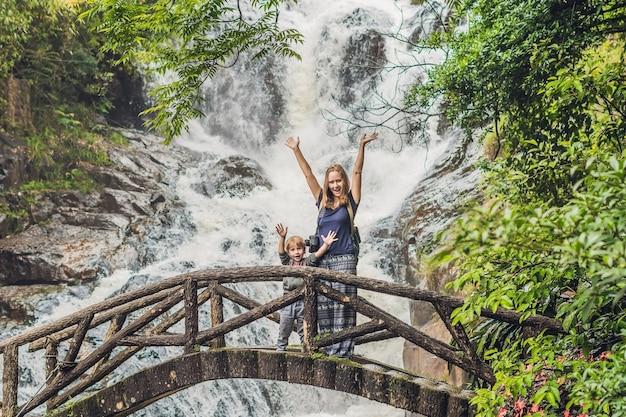 Moeder en zoon op de achtergrond van de prachtige trapsgewijze datanla-waterval in het bergstadje dalat