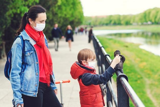 Moeder en zoon op een wandeling met gezichtsmaskers