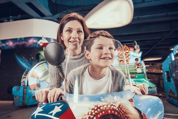 Moeder en zoon op speelgoed motorfiets vakantie samen doorbrengen.