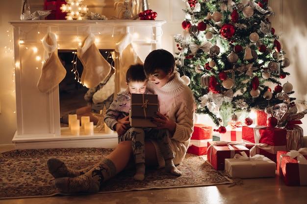 Moeder en zoon openen een kerstcadeau in een doos
