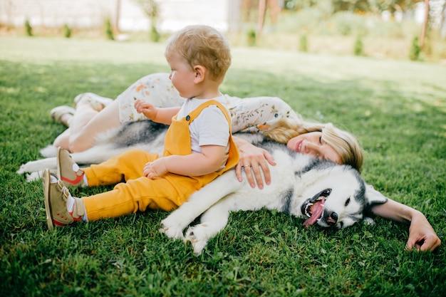 Moeder en zoon poseren met een hond op het gras