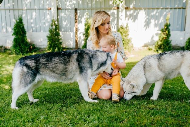Moeder en zoon poseren met twee honden in de tuin