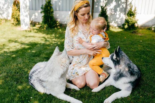 Moeder en zoon poseren met twee honden op het gras
