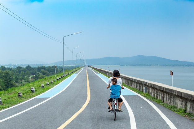Moeder en zoon rijden deze weg op het stuwmeer.