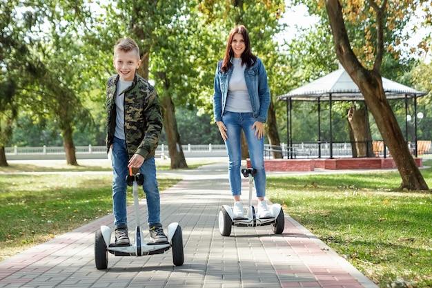 Moeder en zoon rijden op een hoverboard in het park