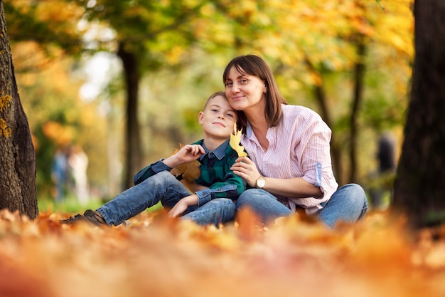 Moeder en zoon rusten in een prachtig kleurrijk herfstpark