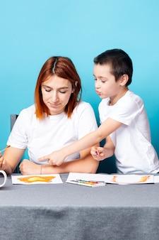 Moeder en zoon schilderen op blauwe ondergrond