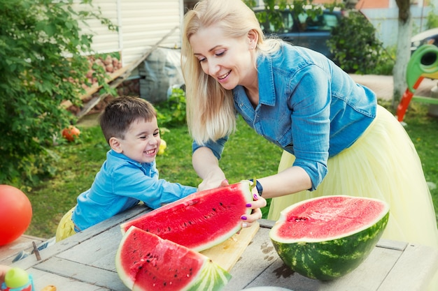 Moeder en zoon snijden een watermeloen en lachen in de tuin. liefde en tederheid.