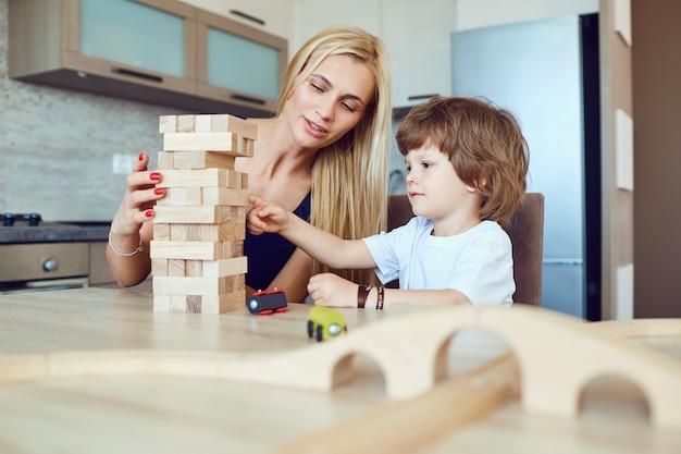 Moeder en zoon spelen binnenshuis aan tafel.