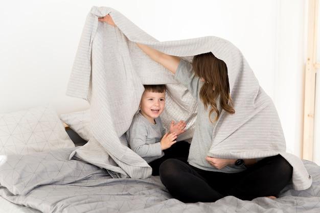 Moeder en zoon spelen in bed