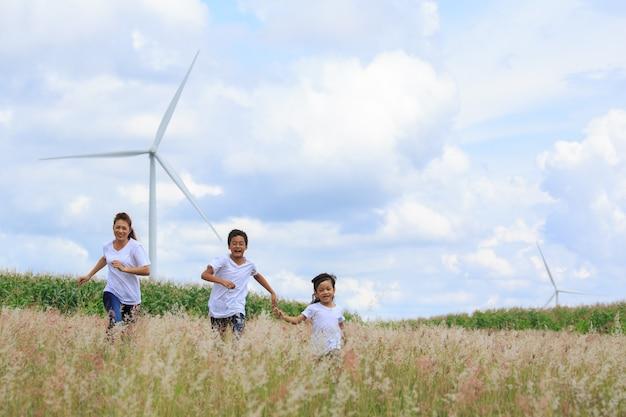 Moeder en zoon spelen in gearchiveerd met enorme windturbine op de achtergrond
