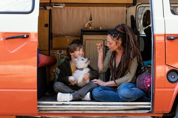 Moeder en zoon spelen met hond op auto