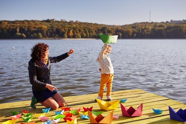 Moeder en zoon spelen met papieren boten aan het meer