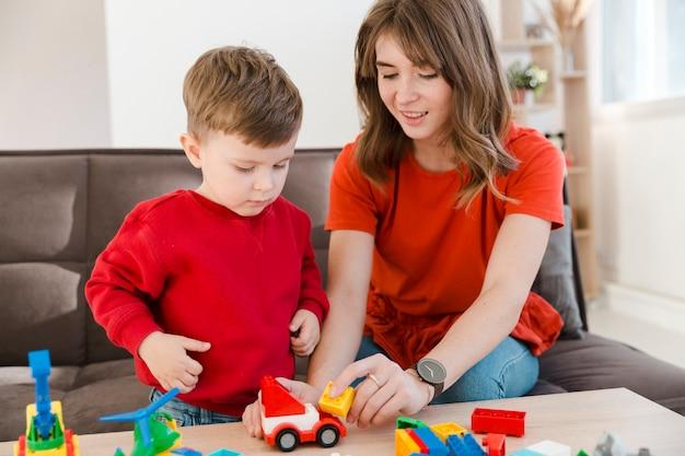 Moeder en zoon spelen met speelgoed