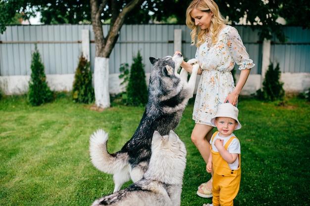 Moeder en zoon spelen met twee honden in de tuin