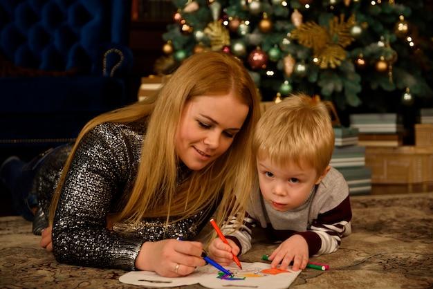 Moeder en zoon spelen op de vloer naast een mooi versierde kerstboom.