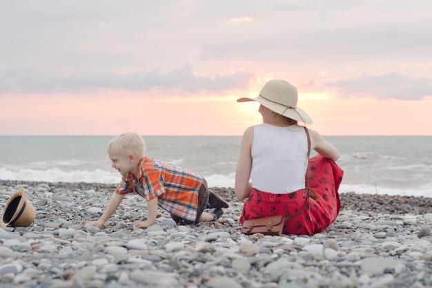 Moeder en zoon spelen op het kiezelstrand. zonsondergang tijd. achteraanzicht