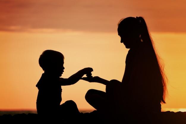 Moeder en zoon spelen op het strand met stenen, silhouetten