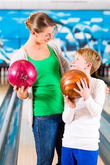 Moeder en zoon spelen samen op bowlingcentrum