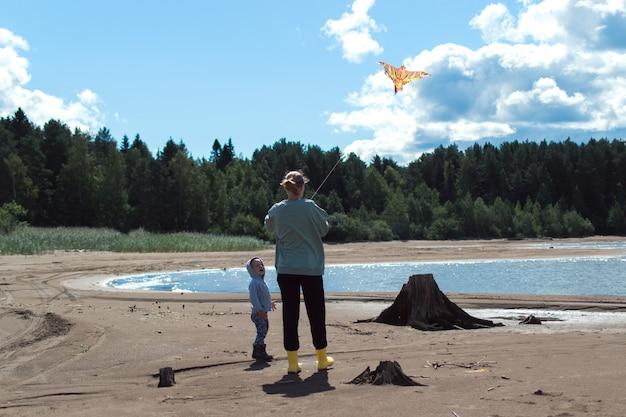 Moeder en zoon spelen vliegeren op de rivieroever