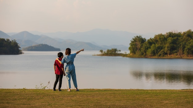 Moeder en zoon staan naast het grote meer en zien uitzicht op de bergen op de achtergrond, moeder wijzende vinger naar bos. idee voor familietoeristen reist samen naar de buitenreis.
