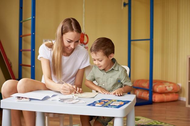 Moeder en zoon tekenen aan een tafel in de kamer.