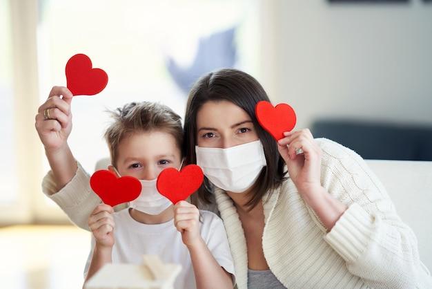 Moeder en zoon thuis in quarantaine tijdens coronaviruspandemie met harten