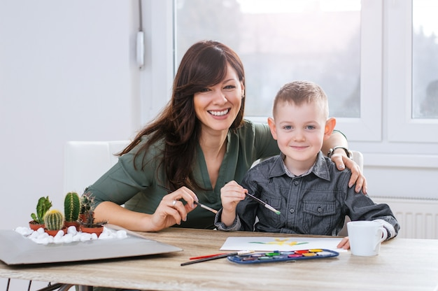 Moeder en zoon thuis schilderen op papier