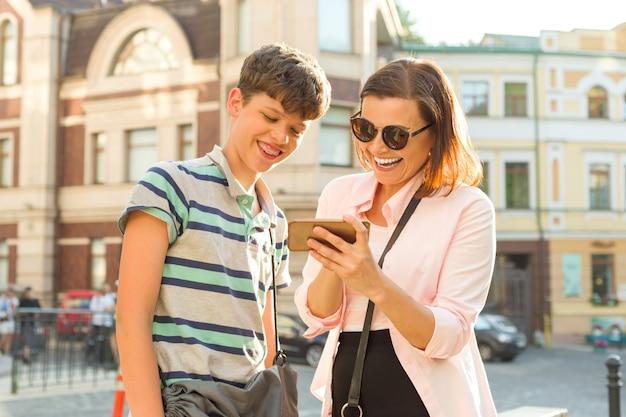 Moeder en zoon tiener kijken naar de mobiele telefoon