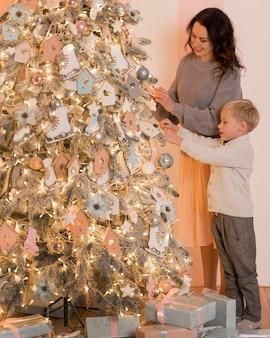 Moeder en zoon versieren het concept van de kerstboom