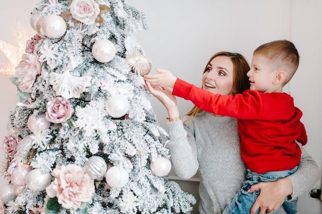 Moeder en zoon versieren kerstboom. vrolijk kerstfeest. kerst versierd interieur. het concept van gezinsvakantie. detailopname.
