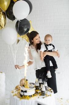 Moeder en zoon vieren de 1e verjaardag samen lachend en lachend met ballonnen, een reep.