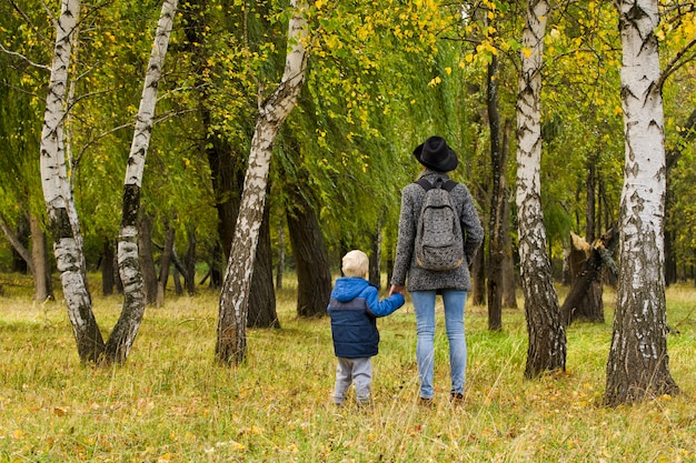 Moeder en zoon wandelen in het bos van de herfst
