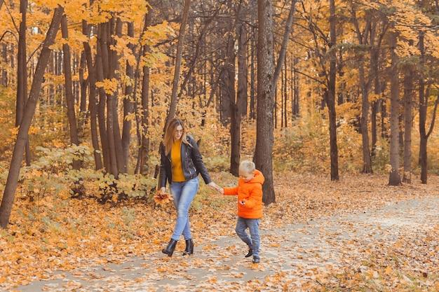 Moeder en zoon wandelen in het herfstpark en genieten van het prachtige herfstseizoen single