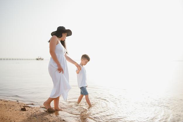 Moeder en zoon wandelen langs het strand