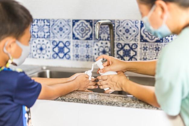 Moeder en zoon wassen hun handen met vloeibare zeep in gootsteen.